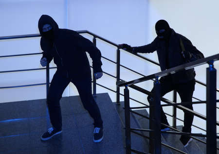 Men in masks with knife on stairs indoors. Dangerous criminals Фото со стока