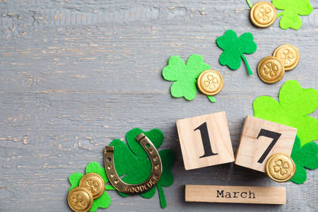 Flat lay composition with horseshoe and block calendar on grey wooden background, space for text. St. Patrick's Day celebration