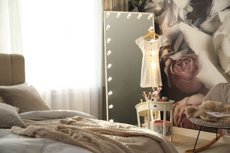 Stylish bedroom interior with lighted mirror and floral wallpaper