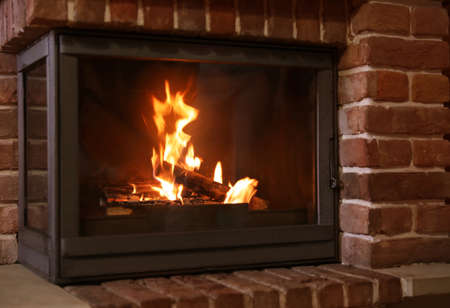 Fireplace with burning wood indoors. Winter vacation