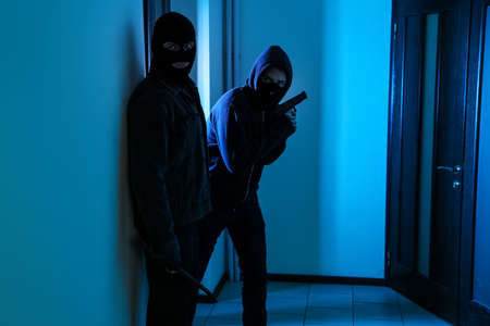 Dangerous criminals with gun and crow bar in hallway Stock Photo