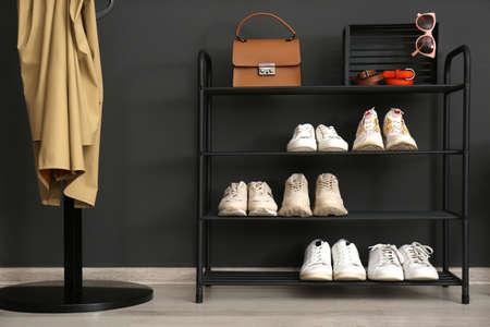 Shelving rack with stylish shoes and accessories near black wall at home. Idea for hallway interior design Foto de archivo
