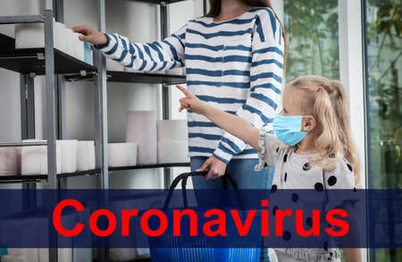 Little girl with medical mask and mother buying toilet paper in shop. Panic of coronavirus outbreak Archivio Fotografico