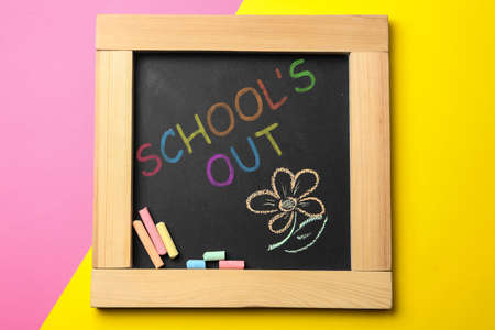 Chalkboard with text SCHOOL'S OUT on color background, top view