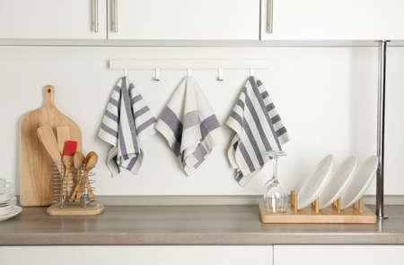 Different kitchen towels hanging on hook rack indoors Banco de Imagens