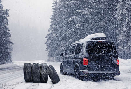 Snow tires near car on road in winter