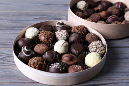 Boxes with tasty chocolate candies on wooden table, closeup