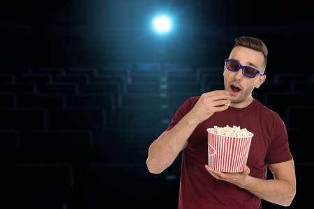 Man with 3D glasses and popcorn in cinema, space for text Stock Photo