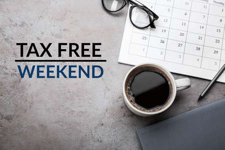 Cup of coffee, stationery and text TAX FREE WEEKEND on grey table, flat lay