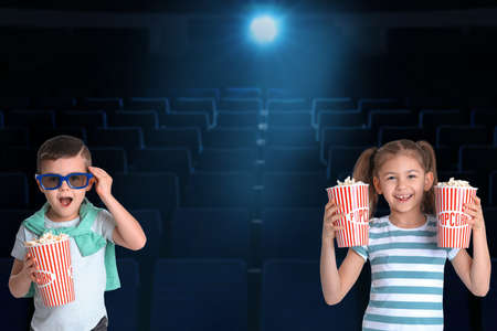 Cute little children with popcorn in cinema hall Banco de Imagens