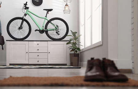 Hallway interior with stylish furniture and green bicycle