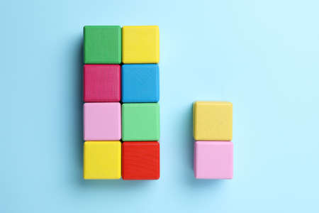 Flat lay composition with colorful cubes on light blue background. Pareto principle concept