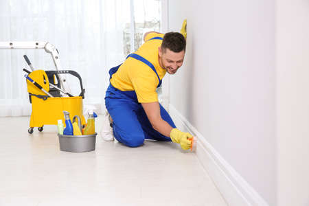 Professional janitor cleaning baseboard with brush after renovation
