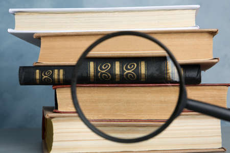 Looking through magnifying glass at stack of vintage books on grey table, closeup. Search concept Фото со стока
