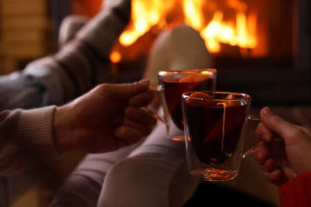 Couple with mulled wine near fireplace indoors, closeup. Winter vacation Stockfoto