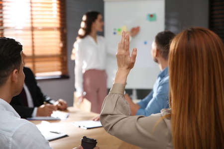 Woman raising hand to ask question at seminar in office, closeup