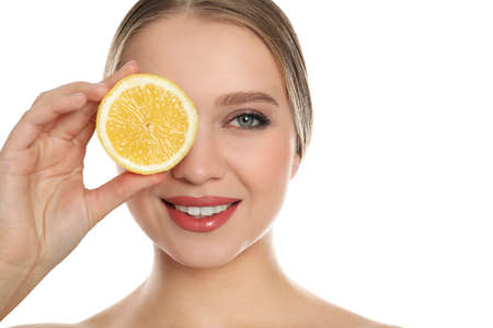 Young woman with cut lemon on white background. Vitamin rich food