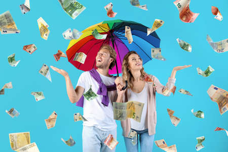 Couple with umbrella under money rain on color background