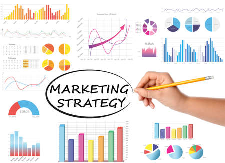 Woman writing words Marketing strategy and charts on white background, closeup Foto de archivo
