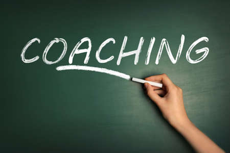 Adult learning. Woman writing word COACHING on green chalkboard, closeup