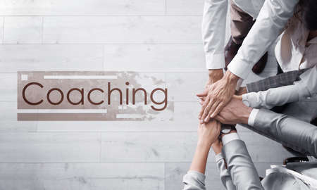 Adult learning. Word Coaching and people holding hands together over light wooden background, top view