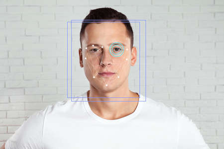 Facial recognition system. Man with scanner frame and digital biometric grid against brick wall