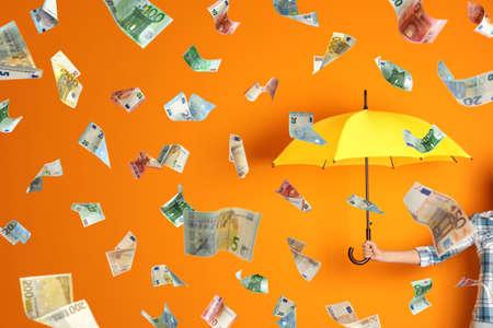 Woman holding umbrella under money rain on color background, closeup