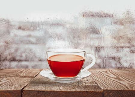 Glass cup of hot tea near window on rainy day Zdjęcie Seryjne