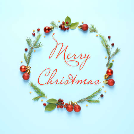 Flat lay composition with text MERRY CHRISTMAS and festive decor on light blue background