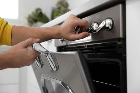 Man using modern oven in kitchen, closeup Banque d'images