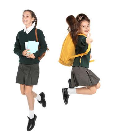 Children in school uniform jumping on white background