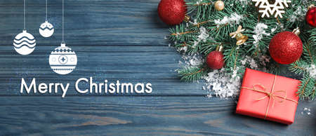 Flat lay composition with text MERRY CHRISTMAS and festive decor on blue wooden background. Banner design