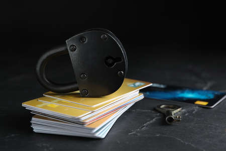 Credit cards, padlock and key on black slate table. Protection from cyber attack