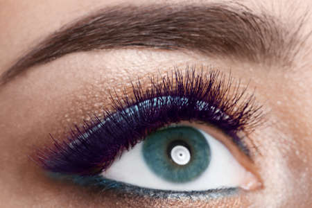 Young woman with color eyelashes and beautiful makeup, closeup