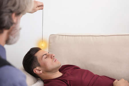 Psychotherapist using pendulum during hypnotherapy   session in office Stockfoto - 147733067