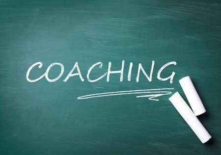 Uczenie się dorosłych. Kawałki białej kredy i napis COACHING na zielonej tablicy, układ płaski