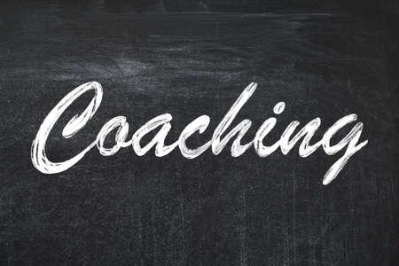 Adult learning. Word Coaching written on black chalkboard
