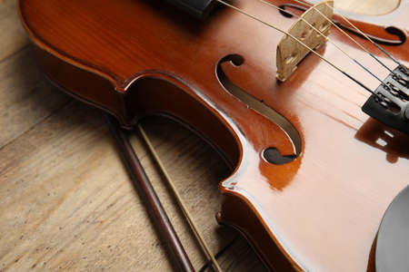 Beautiful violin and bow on wooden table, closeup Stock Photo