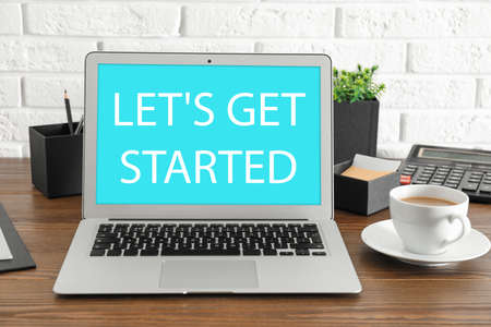 Modern laptop with phrase LET'S GET STARTED and cup of coffee on table