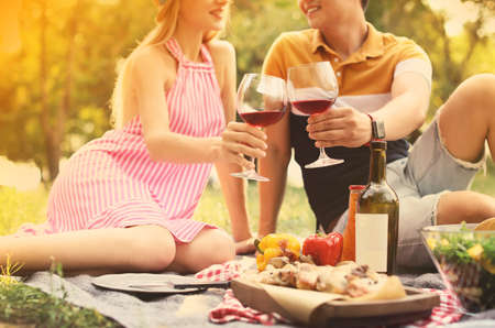 Happy couple with glasses of wine sitting on lawn, closeup. Summer picnic Фото со стока