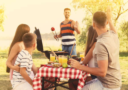 Happy young people and little boy having picnic at table in park on sunny day Archivio Fotografico