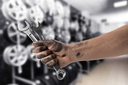 Mechanic with wrenches at tire shop, closeup Foto de archivo
