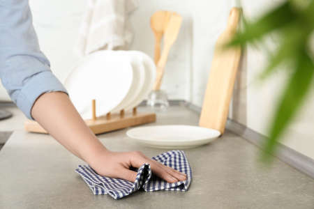 Woman wiping kitchen countertop with towel, closeup