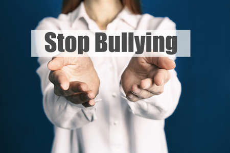 Young woman showing sign STOP BULLYING on blue background, closeup  Stock fotó
