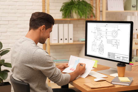 Male engineer working with technical drawing on computer in office