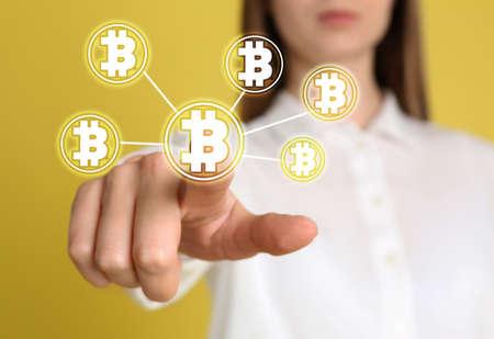 Fintech concept. Woman using virtual screen with bitcoin symbols