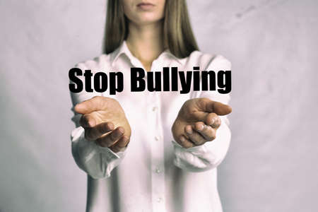 Young woman showing sign STOP BULLYING on light background, closeup