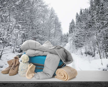 Suitcase with warm clothes on stone surface against beautiful winter landscape Foto de archivo