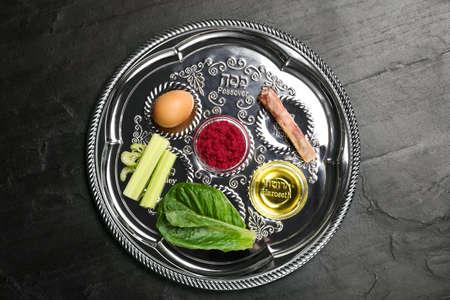 Passover Seder plate (keara) on black table, top view. Pesah celebration