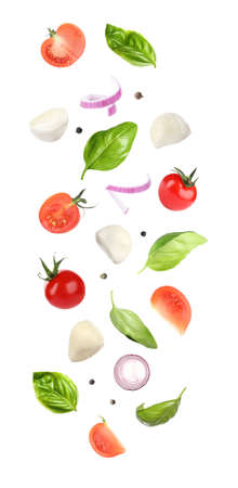 Mozzarella cheese, tomatoes, onion and basil leaves falling on white background